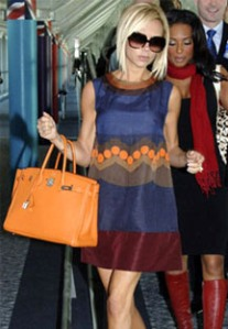 Victoria Beckham is said to have a £1.5 Million Hermes Bag Collection. Here she is with her orange Birkin.