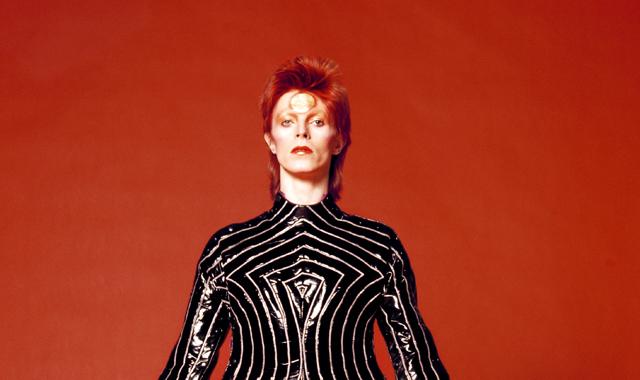 Bowie wearing a striped bodysuit for his 1973 Aladdin Sane Tour designed by Kansai Yamamoto Photo by  Masayoshi Sukita.
